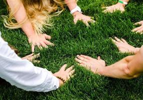 Kreis von Menschen mit Händen auf Gras foto