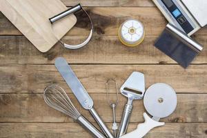 Bäckerei und Kochutensilien mit Küchentimer und Waage auf einem Holztisch foto