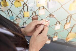 Frauenhand, die ein Schloss auf einem Brückenschienenzaun hält foto