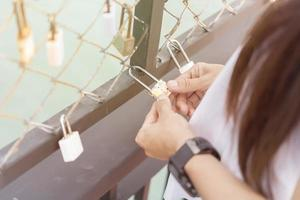 Frauenhand, die ein Schloss auf einem Brückenschienenzaun hält, Schlösser des Liebeskonzepts foto