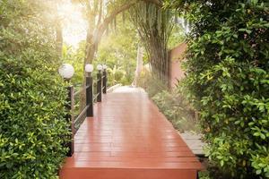 Holzbrücke in einem grünen Park mit Sonnenstrahlen foto