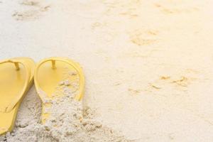 gelbe Sandalen am Strand im Sommer foto
