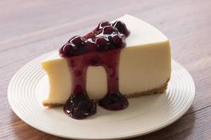 Blaubeercreme-Käsekuchen auf einem weißen Teller auf einem Holztisch foto
