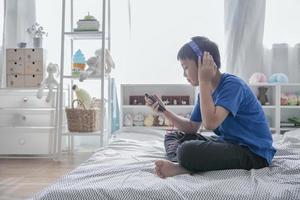 Junge, der Musik mit Kopfhörern hört foto