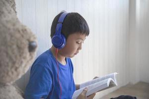 Junge hört zu und liest ein Buch foto