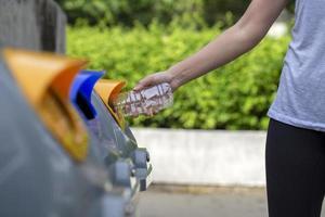Frau, die eine Plastikflasche recycelt foto