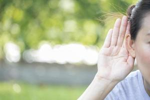 Frau, die ihre Hand nahe ihrem Ohr mit Kopierraum hält foto