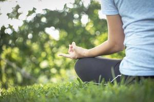 Nahaufnahme einer Frau, die in einem Park meditiert foto