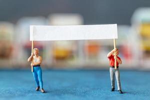 Miniaturmenschen, Demonstranten, die Schilder halten, ihre Hände für die Revolution heben, gegen das Konzept protestieren foto