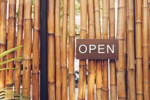 ein Geschäftsschild, das offen sagt, das an einem Türeingang hängt. Vintage Farbton Stil. foto