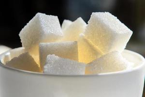 eine weiße Tasse, die bis zum Rand mit Zuckerklumpen gefüllt war foto