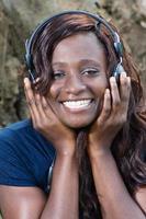 glückliche junge Frau, die gute Musik mit Kopfhörern hört foto