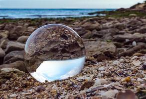 Glaslinsenkugel auf Felsen