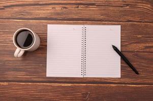 Kaffee und ein Notizbuch auf einem Schreibtisch foto