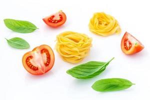 italienisches Nahrungsmittelkonzept der Fettuccine mit Tomate und süßem Basilikum lokalisiert auf einem weißen Hintergrund foto