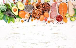 ketogenes kohlenhydratarmes Diätkonzept. Zutaten für die Auswahl gesunder Lebensmittel auf weißem Holzhintergrund. ausgewogene gesunde Inhaltsstoffe von ungesättigten Fetten für Herz und Blutgefäße. foto