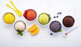 verschiedene Eisgeschmackskugeln auf einem weißen hölzernen Hintergrund. Sommer- und Süßigkeitenmenükonzept. foto