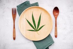 konzeptionelles Bild der Nahrung eines Hanfblattes mit einem Löffel und einer Gabel auf weißem Betonhintergrund foto