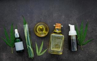 Glasflaschen Hanföl und Hanfblätter auf einem konkreten Hintergrund aufgestellt foto