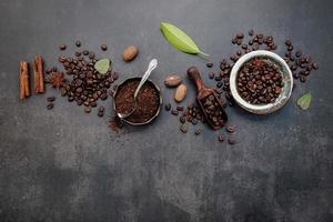 geröstete Kaffeebohnen mit Kaffeepulver und aromatischen Zutaten, um Kaffee auf einem dunklen Steinhintergrund zu machen foto