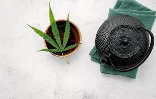 Weinlese-Teekanne mit Kräutertee und einem frischen Hanfblatt auf einem konkreten Hintergrund foto