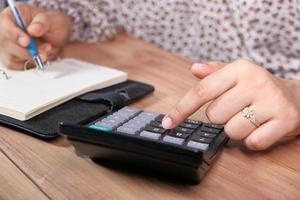 Frauenhand mit Taschenrechner auf Schreibtisch foto