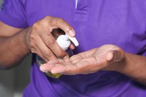 Mann im lila Hemd mit Händedesinfektionsmittel