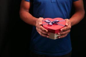 Mann, der herzförmige Geschenkbox lokalisiert auf schwarzem Hintergrund hält foto