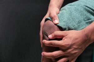 Nahaufnahme des Mannes, der unter Kniegelenkschmerzen leidet, isoliert in Schwarz foto