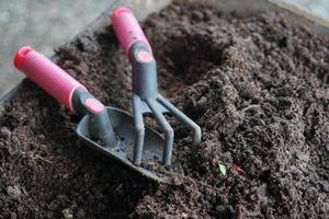 Nahaufnahme von Gartengeräten auf dem fruchtbaren Boden foto
