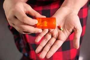 Draufsicht auf die Hände der Frau, die Pillen nehmen