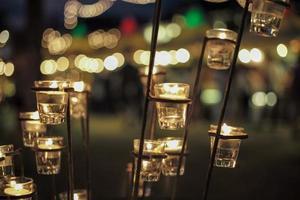 Selektiver Fokus auf Kerzen in kleinen Gläsern mit unscharfen Bokeh-Lichtern im Hintergrund