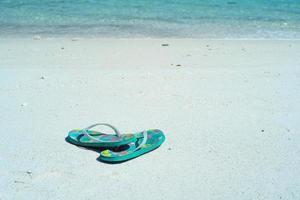 Nahaufnahmepaar alter Sandalen am weißen Sandstrand foto