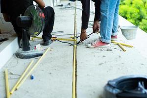 Arbeiter, die den elektrischen Draht und das Rohr im im Bau befindlichen Haus installieren foto