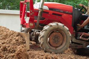 Arbeiter, der den Traktor fährt, um das Bodenniveau zu bestimmen foto