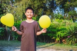 glücklicher Junge, der gelbe Luftballons hält foto