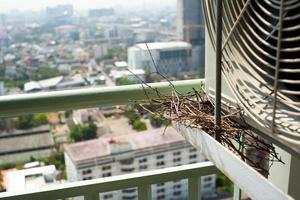 Nahaufnahmevogelnest auf dem Stahlkäfig der Klimaanlage an der Terrasse der hohen Eigentumswohnung mit unscharfem Stadtbildhintergrund foto