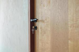 Selektiver Fokus auf modernen Stil des Knopfes an der Holztür mit Schlüsseln, die am Schloss hängen foto