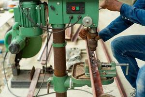Der selektive Fokus der Nahaufnahme auf die Hände des Arbeiters steuert die elektrische Bohrmaschine zum Bohren des Lochs in der Winkelstahlstange auf der Baustelle foto