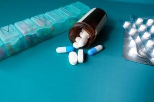 Kapsel und Pillen, die auf grünem Hintergrund verschütten