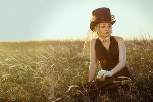junges blondes Mädchen in einem braunen Weinlesekleid und Zylinder im Gras foto