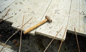 Hammer legt auf den Bewehrungsstahl des Betonbodens foto