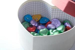 kleine herzförmige Geschenkbox mit Süßigkeiten auf weißem Hintergrund foto