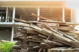 Nahaufnahmehaufen des Holzes mit unscharfem Haus im Bau im Hintergrund foto