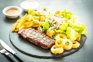 Gegrilltes Rinderfleischsteak mit Pommes Frites Zwiebelring mit Sauce und frischem Gemüse