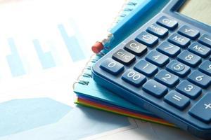 Nahaufnahme des blauen Rechners und des Finanzdiagramms auf Tabelle