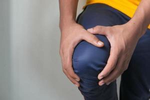 Mann hält Knie in Schmerzen foto