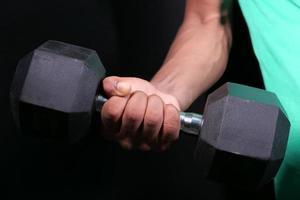 Hand des jungen Mannes, der mit Hanteln drinnen trainiert