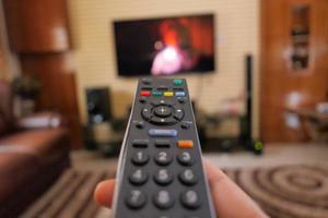 Hand hält TV-Fernbedienung in einem Wohnzimmer