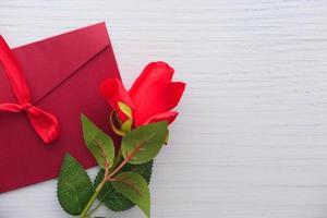 Umschlag und Rosenblume auf weißem Hintergrund mit Kopienraum
